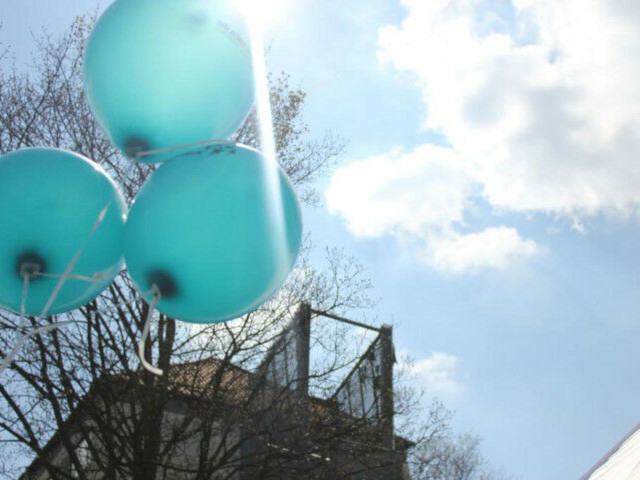 Three balloons in front of a blue sky