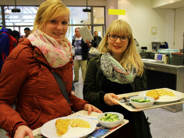 Two young women with trays and plates filled with food